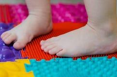 Feet on an orthopedic mattress. Littlechildren`s feet on an orthopedic mat stock photography