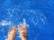 Feet over a pool Royalty Free Stock Photography
