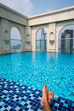 Feet over the sparkling pool on top of building with Saigon aeri Royalty Free Stock Image