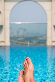 Feet over the sparkling pool on top of building with Saigon aeri Stock Photo