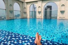 Feet over the sparkling pool on top of building with Saigon aeri Stock Photos