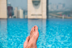 Feet over the sparkling pool on top of building with Saigon aeri Royalty Free Stock Photography