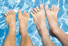 Feet Over the Swimming Pool. Man and woman's feet over the swimming pool Royalty Free Stock Image