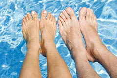 Feet Over the Swimming Pool. Man and woman's feet over the swimming pool Stock Image