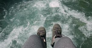 Feet over water river sitting on bridge edge Travel Lifestyle concept. Adventure vacations outdoor stock footage