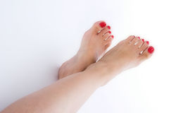 Feet over white. Feet crossed over white with red nails Royalty Free Stock Photo