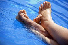 Feet paddling in clear swimming pool water. Feet of a woman and a man paddling in the blue water of a swimming pool Stock Images