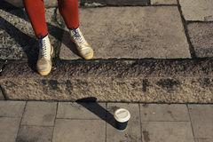 Feet and paper cup in street Royalty Free Stock Photo
