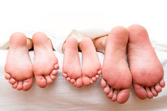 Feet of parents and child on the bed Stock Photography
