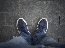 Feet on the pavement. Feet with shoes on the pavement Stock Photo