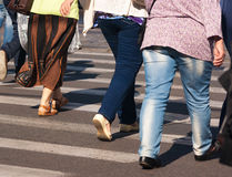 Feet of the pedestrian on city street. Feet of elderly pedestrians walking on the crosswalk on summer day Royalty Free Stock Photography