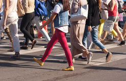 Feet of the pedestrians crossing on city street. Feet of young pedestrians walking on the crosswalk on summer day Stock Photography