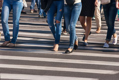 Feet of pedestrians walking on the crosswalk Royalty Free Stock Photos