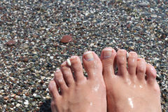 Feet with pedicure on the beach Royalty Free Stock Image
