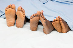 Feet of people lying in bed Royalty Free Stock Images