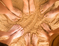 Feet of people standing alone on the sand. Beach Stock Photo