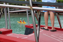 Feet of the people on the tour boat and kayak activities background. stock photo