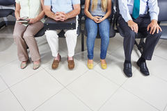 Feet of people in waiting room. Feet of different people sitting in a waiting room Royalty Free Stock Image