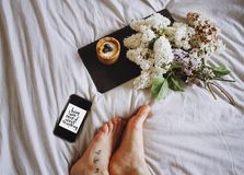 Feet of person on bed with flowers