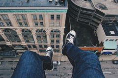 Feet of person on edge of high building Stock Image