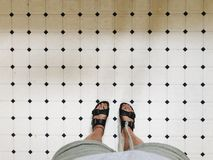 Feet of a person in sandals on white tiles in a bathroom