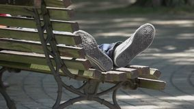 Feet of a person sleeping in a public park