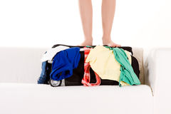 Feet of person on suitcase. Closeup of a person's feet, standing on a full and overflowing suitcase filled with summer clothes. White background royalty free stock images