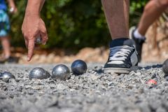 Petanque player pointing at the ground, holding a steel ball. The feet of a petanque player pointing at the ground, holding a steel ball stock photo