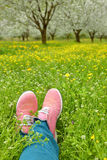 Feet in pink shoes on green field Stock Photography