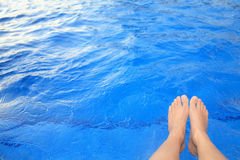 Feet beside the pool. The feet with blue pool background Royalty Free Stock Photo