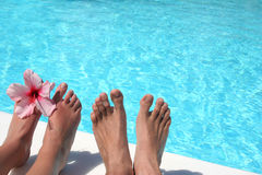 Feet Pool. Man and women's feet by bright pool Royalty Free Stock Image