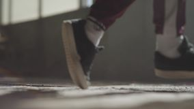 Feet of a professional dancer in sneakers dancing on a dusty concrete floor in an abandoned house. Feet in sneakers of a professional dancer dancing on a dusty stock video footage