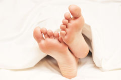 Feet protruded from blanket Stock Photography