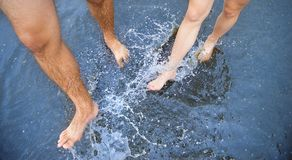 Feet in puddle Stock Images