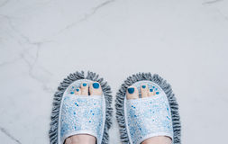 Feet in quirky slippers that are also a mop Stock Photos