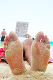 Feet and reading book. On the beach in summer day Stock Images