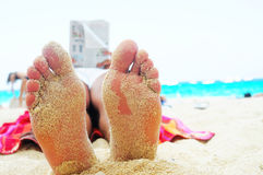 Feet and reading book. On the beach in summer day Royalty Free Stock Image