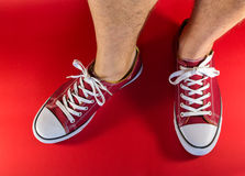 Feet and Red Canvas Trainers Royalty Free Stock Images
