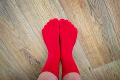 Feet in red finger socks. On wooden floor stock images