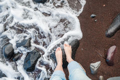 Feet on a red sandy beach Royalty Free Stock Photo