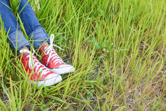 Feet red sneaker a girl in nature Royalty Free Stock Photos