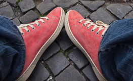 Feet in red sneakers and jeans outdoors. Royalty Free Stock Photography