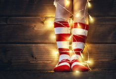Feet in red and white socks. Merry Christmas and Happy Holiday! Baby feet in red and white socks with a festive garland on wooden background Stock Photos