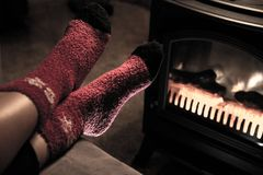Feet in Red Woolen Christmas Socks by Fireplace. Feet in Red Woolen Christmas Socks by a Fireplace Royalty Free Stock Photos