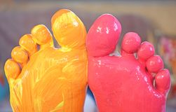 Feet in red and yellow paint. Beautiful royalty free stock photo