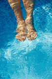 Feet refreshing in swimming pool. Photo of a feet refreshing in swimming pool in summer Stock Images