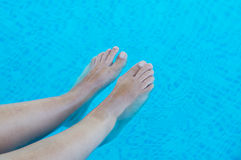 Feet refreshing in swimming pool Royalty Free Stock Photos