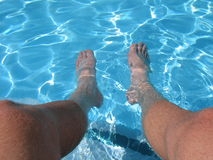 Feet Relax in Pool Water. Tan feet hanging off edge of pool into water Stock Image