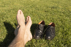 Feet relaxing in the grass. With his shoes royalty free stock photos