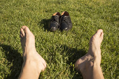 Feet relaxing in the grass. With his shoes stock image